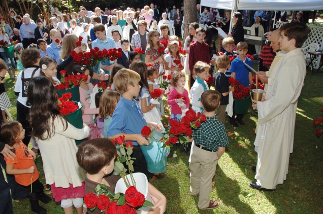 """Children come in procession for """"the blessing of the roses."""""""