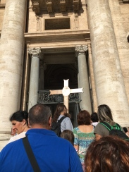 Pilgrims carrying the Jubilee of Mercy Cross into the Holy Door of St. Peter's